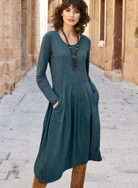 A contemporary spin on the casual t-shirt dress. Sewn of drapy pima (49%) modal (47%) and spandex (4%) jersey and intriguingly finished with angled seaming and dipping hemline. Gathers at one side create a bubble hem silhouette; pockets.