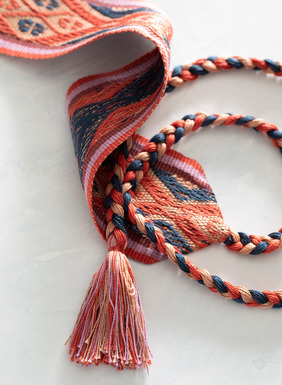 The belt is handwoven of traditional Peruvian geometrics in sunset hues of papaya, pink, violet and blue pima with braided ties tipped with fringe.