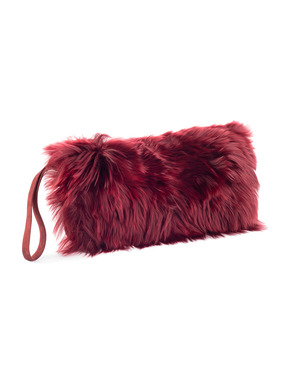 The suede clutch folds over to alpaca fur. Wristlet strap; snap closure.