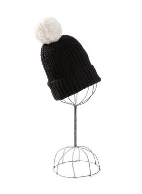 Ein Pompon aus weißem Alpakafell krönt die dicke Strickmütze aus schwarzem Babyalpaka.