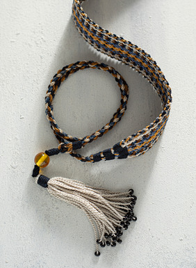 Handcrocheted in earthen stripes of cream, umber, gold and dusty blue of pima; bead-tipped tassel ties.