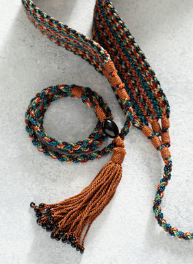 Stripes of paprika, teal, cerulean, brass and dusty rose are lit with a touch of metallic thread in our hancrocheted belt with braided ties and bead tipped tassels.