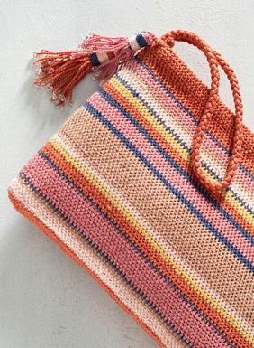 Handcrocheted in bright stripes, the artisan-crafted pima bag has a zip top and wrist strap.  Lined with an interior pocket.