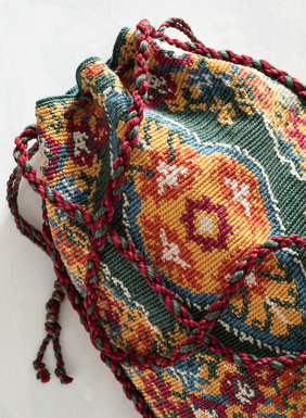 The handcrocheted pima bag conjures ancient tapestry work. Braided shoulder strap; drawstring closure; twisted tassels; lined with an interior pocket.