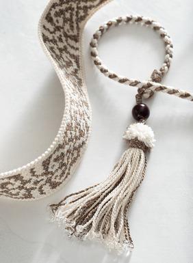 Der handgehäkelte, crèmefarbene Pima-Gürtel mit Inka-Motiven hat geflochtene Quasten-Bindebänder.