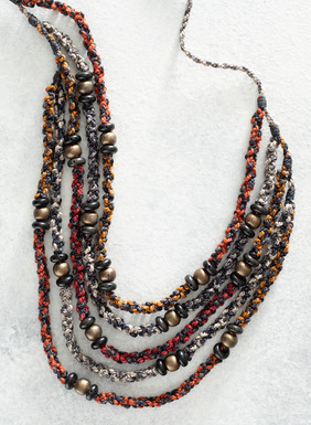 This adjustable, multi-strand statement necklace was handcrocheted in Peru by skilled textile artists. It features a striking blend of red, orange, yellow, dusty blue, and creamy pima cotton (87%), interwoven with shimmery silver Lurex® (13%) and dotted with antique brass-colored beads. A wonderful travel piece, this lightweight and handmade necklace can be dressed up or down. Sales support Peruvian cottage industries working to preserve traditional textile techniques.