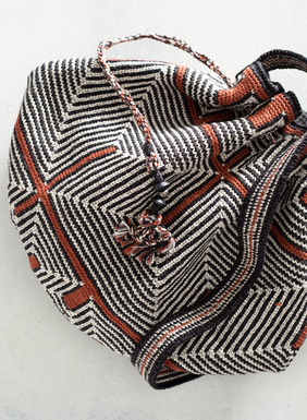A true work of art, this bucket bag was handcrocheted in Peru by masterful textile artist. It features Andean geometrics of black and cream accented with burnt orange pima cotton (93%) and interwoven with silver metallic threads (7%). Big enough to fit your daily essentials and a few extra treasures, it includes a drawstring closure for extra security, one interior pocket, and a shoulder strap. Sales support Peruvian cottage industries working to preserve traditional textile techniques.