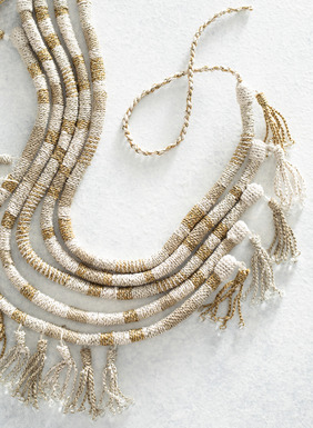 Hand-wrapped in Peru, this lightweight and versatile statement necklace features shades of tan, cream, and sand-colored pima (62%) with whispers of gold metallic thread (38%). The adjustable, 5-cord necklace is trimmed in tassel fringe with glass beads. All sales support Peruvian cottage industries working to preserve traditional textile techniques.