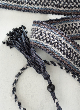 Handcrocheted in Peru by masterful textile artists, this 1 ½-inch wide belt features shades of navy, chambray, and taupe pima cotton (90%) interwoven with shimmery metallic thread (10%). The braided ties are tipped with tassels for a worldly finish. A wonderful travel accessory, this lightweight handmade belt can be dressed up or down. Sales support Peruvian cottage industries working to preserve traditional textile techniques.