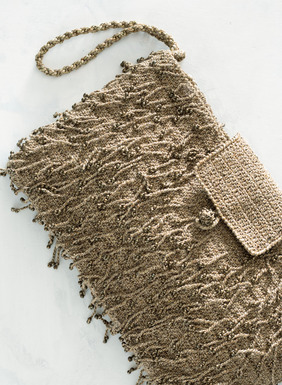 The handcrocheted pima wristlet clutch is covered with beaded fringe and lit with gold metallic threads for shimmer. Lined with a single interior pocket, zip closure.