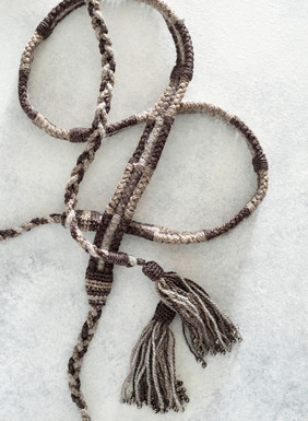 The artisan belt is handbraided and finished with beaded tassel ties.