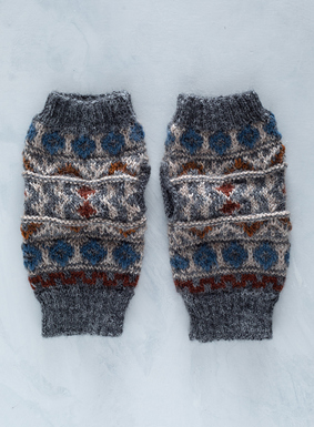 The folk inspired fingerless gloves are handknit of cozy alpaca (56%), baby alpaca (40%) and wool (4%) in earthy shades of blue and brown.
