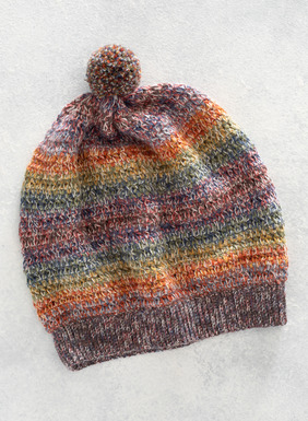 A lighthearted wintry accent, the hat is artisan-knit and striped in pastels of baby alpaca (77%) and wool (23%).
