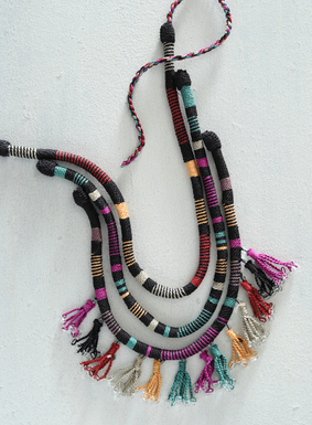 The show-stopping accessory is a triple-strand necklace of colorful, handwrapped Peruvian pima cotton, fringed with glass bead-tipped tassels. Varying stripes of yellow, burnt orange, stone, purple, and light teal are grounded on black for a dramatic finishing touch.