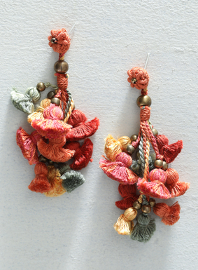 Take any outfit from ordinary to extraordinary with our statement-making earrings.  A festive cascade of colorful tassels and brass beads, these handmade earrings feature bold shades of sage, orange, gold, and coral Peruvian pima cotton yarns.