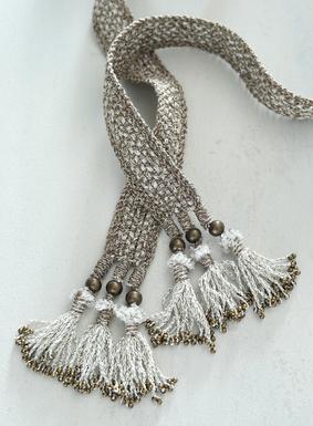 Der von peruanischen Kunsthandwerkerinnen handgeflochtene Gürtel aus 92 % peruanischer Pimabaumwolle und 8 % goldschimmernden Metallicfäden setzt einen leuchtenden Akzent.