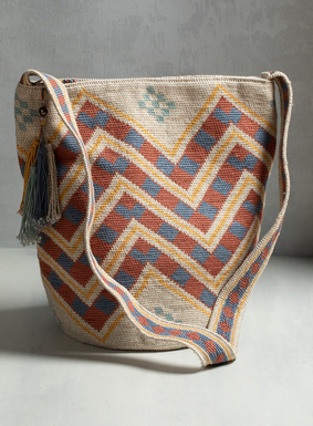 Our work-of-art pima bag is crocheted by hand in colorful chevron stripes of creamy gold, dusty blue, and terra cotta.  Adorned with beaded tassels and a patterned crossbody strap, the bag is also fully lined with an inside pocket and zip closure for security.