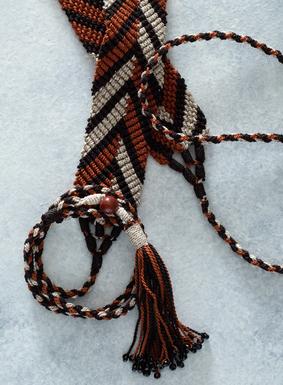 Ein aufsehenerregendes Accessoire für jeden Look: Unser Gürtel mit Zickzackmuster wird von Meistern der Strickkunst aus melierten Garnen in Sand, Braun und Orange handgehäkelt. Aus peruanischer Pimabaumwolle. Vollendet mit Bindebändern, die in Quasten mit schwarzen Glasperlen enden.