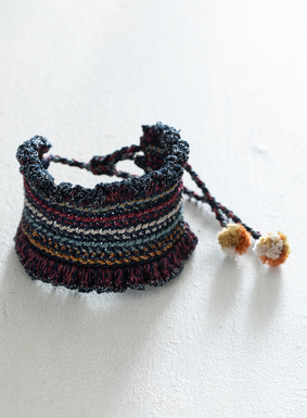 Schick einzeln oder in Kombination tragbar: Unser Armband ziert eine ganze Farbpalette an bunten Streifen aus Pimabaumwolle.  Seitenrüschen in Marineblau mit Lurexfäden bringen das Armband zum Glänzen. Verstellbar mit einem mehrfarbigen Bindeband mit Pomponverzierung.
