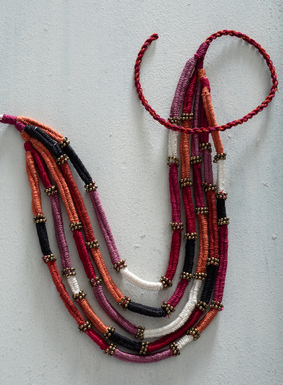 Statement-making necklaces can instantly elevate a simple tee to extraordinary.  Our bold Peruvian pima necklace is made by hand, with yarns twisted in shades of orange, pink, persimmon, magenta, black and ivory.  Antique brass spacers and an adjustable tie closure finish the necklace.