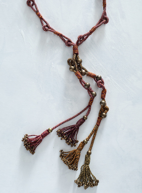 Tweeded yarns of shimmery pima and metallic thread are adorned with brass beads and tassels in this versatile necklace.  Adjustable ties offer a variety of styling options.