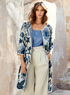 The showstopping jacquard-knit duster is patterned in Dutch porcelain florals of navy, indigo and chambray on ivory pima. Styled with a round neck, ¾-sleeves and pockets, it closes with an interior button-and-loop closure at the waist for a flyaway shape.