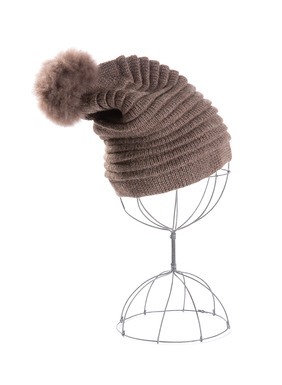 Die Mütze ist mit Ottoman-Muster rippengestrickt und hat einen Pompon aus Alpakafell.