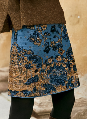 The chic A-line mini-skirt, in chintz florals of midnight and copper on a dusky blue ground. Jacquard knit of pima (90%) and gold metallic (10%) yarns for festive sparkle.