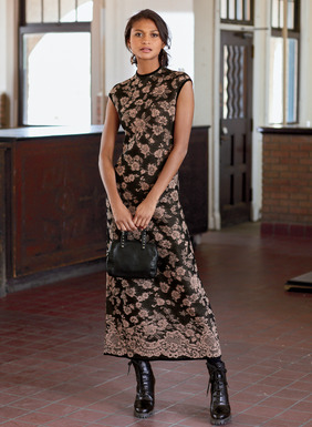 Borrowing its patterning from an antique lace remnant, this alluring pima jacquard knit dress showcases ashes-of-rose blooms on a textural black ground. The Asian-inspired silhouette is styled with a high neck, shoulder capping sleeves, buttoning keyhole back closure and back slit.