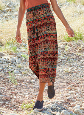 In spicy paprika, Sedona red, camel and turquoise, intricate geometrics from an antique Moroccan carpet pattern the pima jacquard column skirt; single side slit.