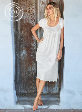 Delicate smocking and handcrochet scallops embellish the yoke of our romantic white pima jersey nightgown. Finished with pretty raglan puff sleeves and a lettuce-edged hem.