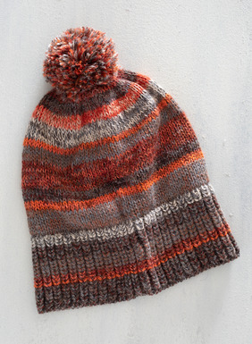 Tweeded desert hues stripe the pima (64%) and alpaca (36%) pompom hat.