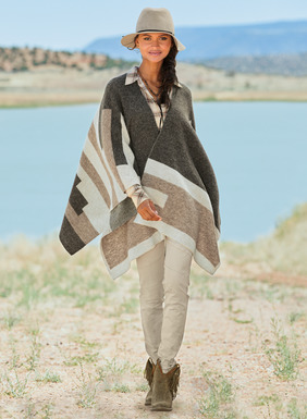 Usher in the season with our boho-chic ruana, a soft, effortless layer of frothy baby alpaca (60%), nylon (35%) and merino wool (5%). This statement piece is knit in broad bands and stepped Southwestern geometrics, in a palette of sophisticated neutrals.