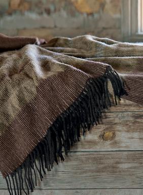Die doppellagige Decke hat mit Inkamotiven verzierte Streifen in Wüstenfarbtönen. Aus Alpaka (50 %), Wolle (35 %), Acryl (8 %) und Nylon (7 %) jacquardgewebt; Fransenkante.