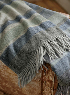 Keep the chill at bay with this snuggly-soft layer of double-faced alpaca (50%), wool (35%), acrylic (8%) and nylon (7%). Dusty blue stripes with fringe at both ends.
