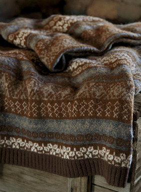 Cozy warmth for bed, sofa or cabin, our soft knit throw channels a vintage Fair Isle sweater, in brown, dusty blue and snow alpaca (64%), wool (17%), acrylic (12%) and nylon (7%).
