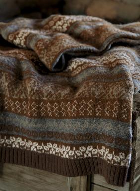 Mollig warm: Unsere weiche Strickdecke aus 64 % Alpaka, 17 % Wolle, 12 % Acryl und 7 % Nylon zieren Fair-Isle-Muster in Braun, gedecktem Blau und Schneeweiß.