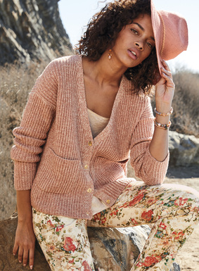The lofty, boxy cardigan is rib knit in tweeded, rosy hues of pima (88%) and nylon (12%) bouclé yarns, with a deep v-neck, drop shoulders and patch pockets.
