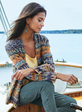 Unser Cardigan hat abstrakte geometrische Muster in Blau- und gedeckten Koralletönen. Mit einer gerollten Blende schlicht vollendet. 95 % Pimabaumwolle; 5 % Metallicfäden.