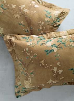 We've reinterpreted one of our signature prints as a luxurious collection for the bed. Flowering magnolia blossoms from a Chinese embroidery wash across a luminous gold ground of the silky cotton sateen sham; mother-of-pearl button closures.