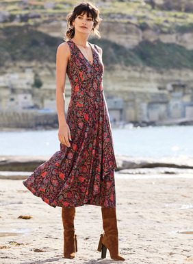Art nouveau florals  in bright jewel tones on an aubergine ground climb the romantic tea-length dress. In drapy viscose (95%) and elastane (5%) jersey, it's shaped to flatter with a faux wrap v-neck and seamed waist that releases in asymmetrical pleats to a fluttering, angled hem.