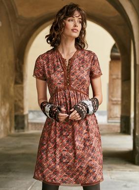 Das Georgette-Kleid im 40er-Jahre-Stil aus 53 % Viskose und 47 % Rayon ziert ein Tapetenmuster mit Rosen auf schrägen Karos und ist mit einem Bogenrand aus Swiss-Dot-Spitze eingefasst. Messingknöpfe am Oberteil; die gerundete Taillennaht weitet sich in Falten zum ausgestellten Saum.