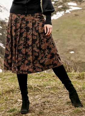 Maple and gold peonies from an embroidered Japanese textile are traced on the soft black Tencel® skirt. Fitted through the asymmetrical yoke, it releases with soft knife pleats to an A-line hem.