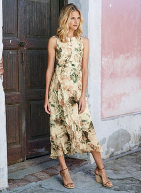 A stunner for warm-weather occasions, in an artistic montage of watercolor blooms. The soft viscose (95%) and elastane (5%) jersey bodice fits through the angled seamed waist and releases to a diaphanous, woven viscose skirt with faux wrap panel and floaty ruffled hem. Finished with a high neckline and contoured shoulders; lined skirt.
