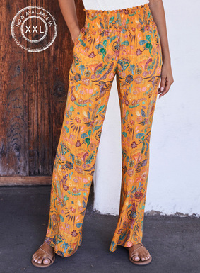 Illustrated in birds and botanicals on a bright mango ground, the viscose palazzo pants have a smocked waist, pockets and flowy, wide legs.
