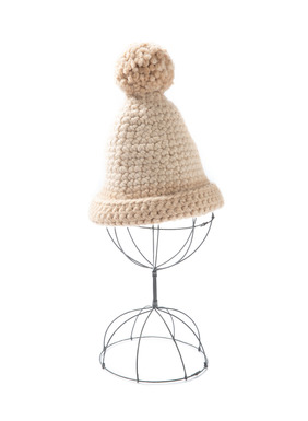 The wintry hat is densely crocheted in an ombré of taupe and caramel alpaca and topped with a pompom.