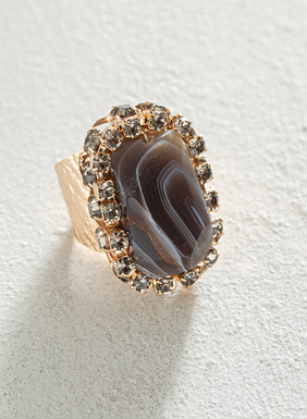 The handmade eye-catching cocktail ring features a rough-cut agate framed in crystals, perched atop a hammered gold plate setting. Adjustable band.