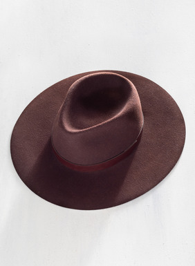 The handblocked black wool felt hat features a wide brim and leather band.