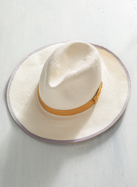 The jaunty hat, handwoven of cream straw with amber grosgrain ribbon and contrast stitching.