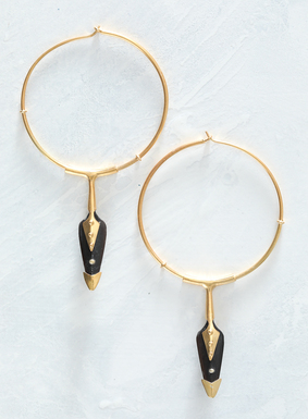 Artisanal accessories at their finest, our kinetic, golden vermeil hoop earrings suspend black horn arrowhead-shaped charms. The arrows are embellished with golden tips. Fiercely beautiful, these earrings are a true display of expert craftsmanship.